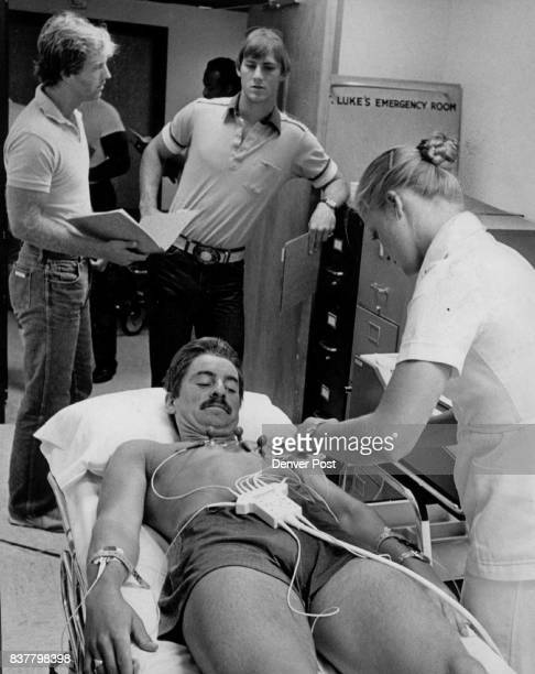 Football Denver Broncos Training Camp ' You Sure this isn't Gonna Hurt ' Before on EKG test Anne Paluh applies the wires to wary kicker Roy Geiger...