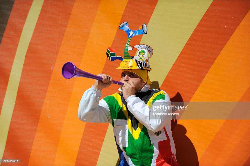A football fan from South Africa wearing a Makarapa hat and blowing a Vuvuzela horn