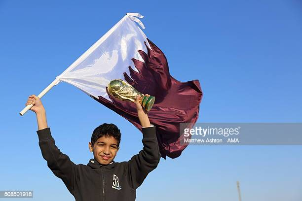 A football fan holding the maroon and white national flag of Qatar with a replica of the FIFA World Cup Trophy in Doha Qatar the host venue for the...