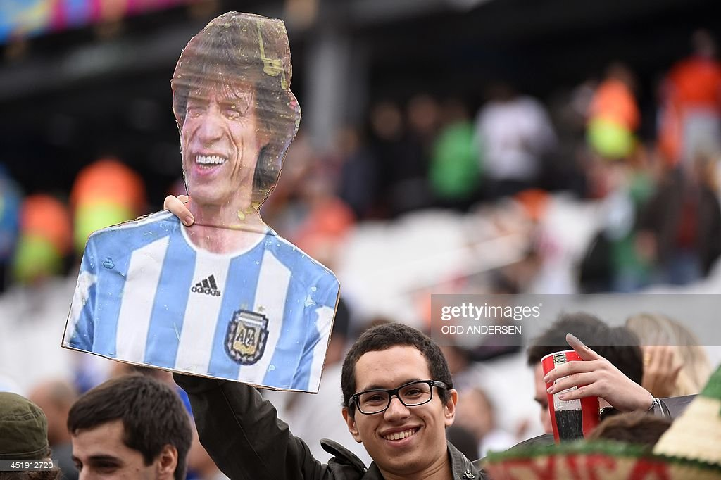 A football fan holds a cardboard cutout of The Rolling Stones' Mick Jagger prior to the semi-final football match between Netherlands and Argentina of the FIFA World Cup at The Corinthians Arena in Sao Paulo on July 9, 2014.