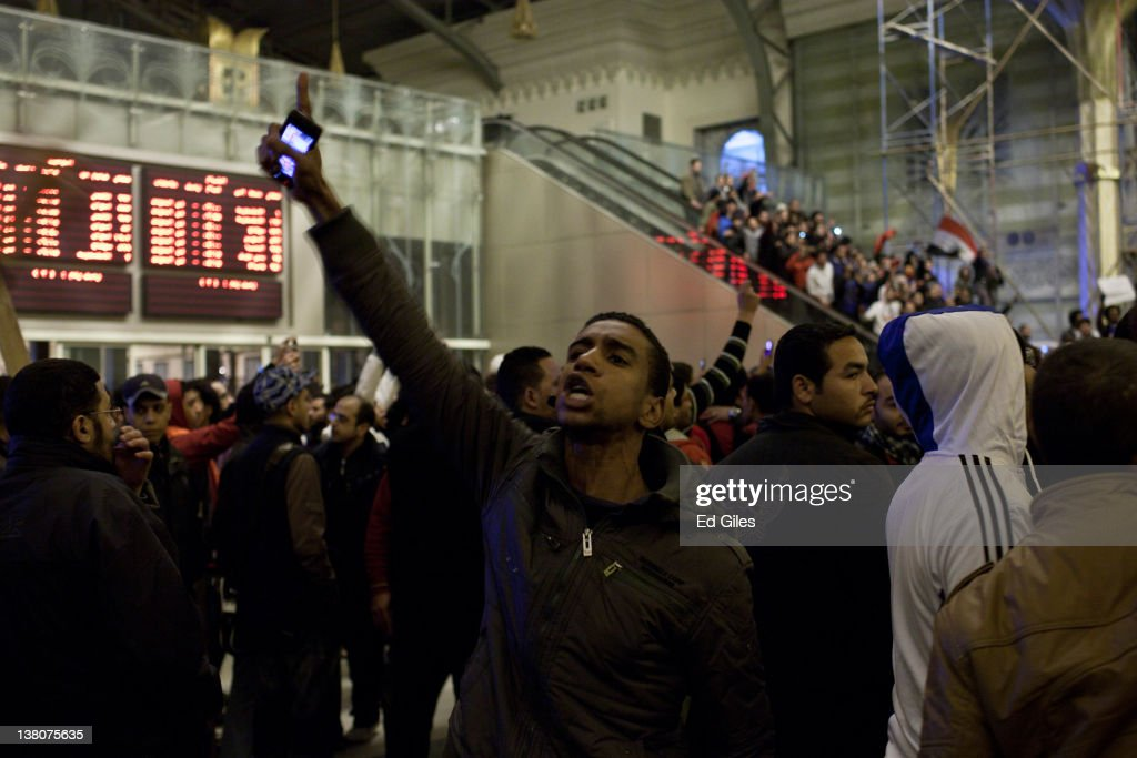 A football fan holds up his phone and shouts during a gathering of mourners at Cairo's railway station as they receive the bodies of 74 football fans...