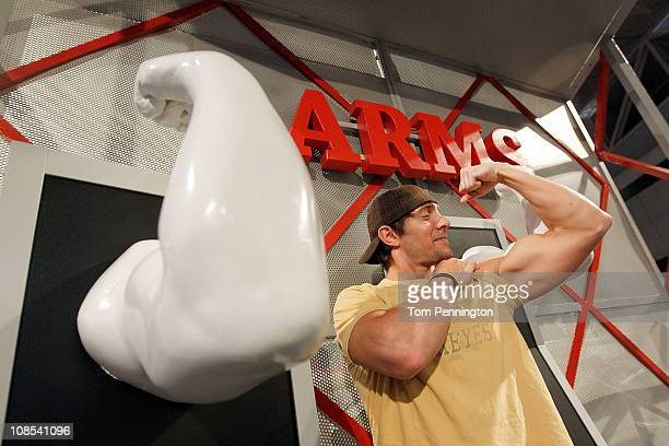 Football fan Nate Sulzner compares his arm to a cast of an NFL player's arm at the NFL Experience exhibit at the Dallas Convention Center on January...
