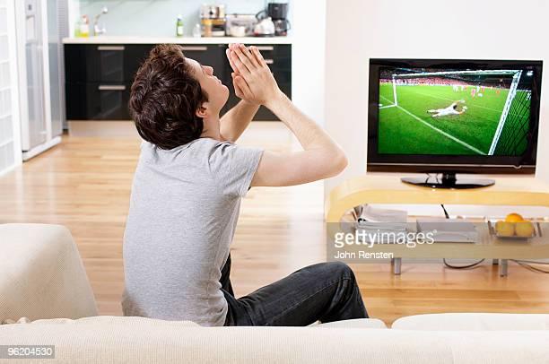 football fan prays as goal scored on television