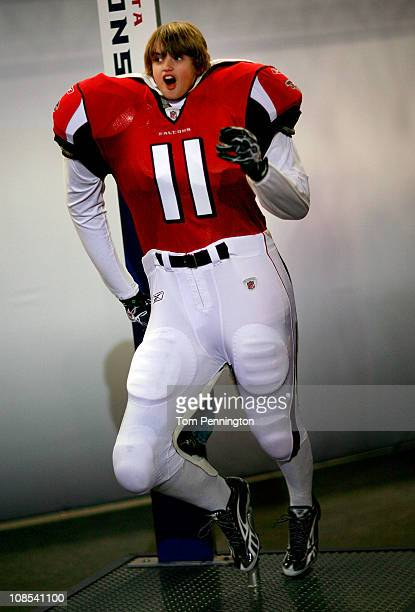 Football fan Reed Dearnbarger poses behind an Arlanta Falcons uniform at the NFL Experience exhibit at the Dallas Convention Center on January 29...