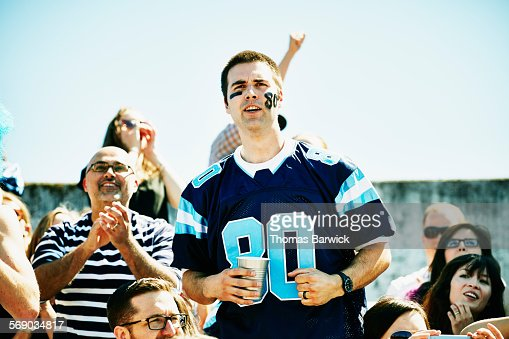 Football fan standing in stadium cheering