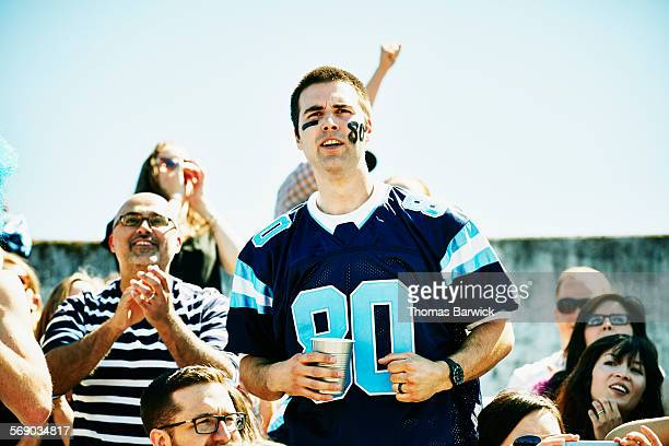 Football fan standing in stadium cheering