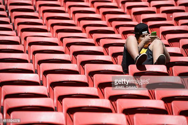 A football fan uses his mobile phone prior to a Round of 16 football match between France and Nigeria at Mane Garrincha National Stadium in Brasilia...