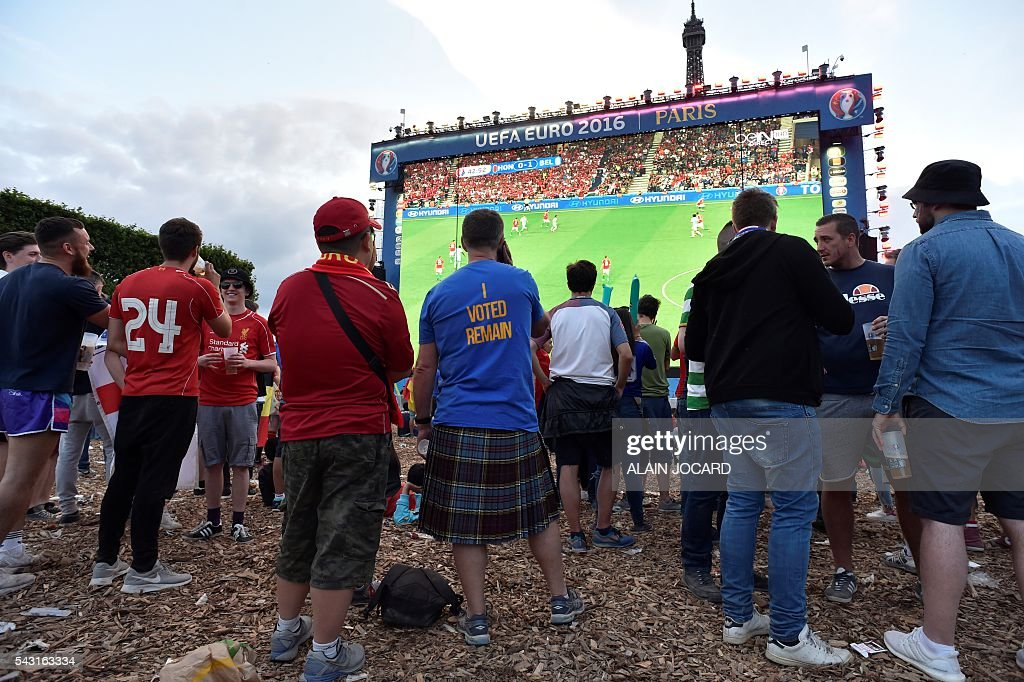 A football fan wearing a shirt reading 'I voted remain' watches on a giant screen the Euro 2016 round of 16 football match between Hungary and Belgium at the Champs-de-Mars fan zone in Paris on June 26, 2016. / AFP / ALAIN