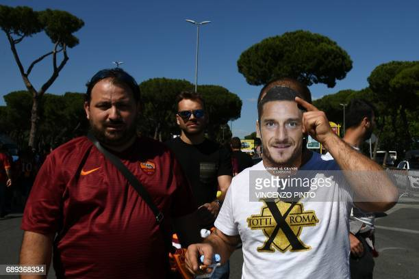 A football fan wears a mask showing a portrait of AS Roma's captain Francesco Totti as he arrives at the Olympic Stadium for the Italian Serie A...