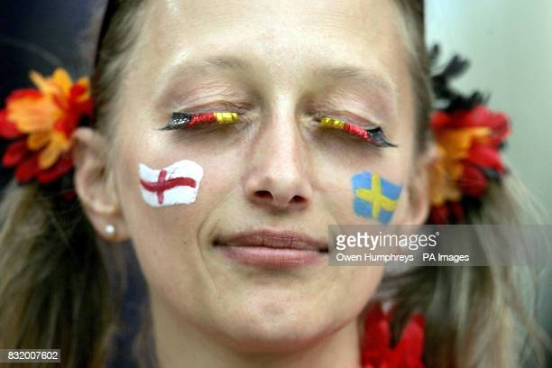 A football fan with German flag eyelashes and a a Swedish flag on her left cheek and a Swedish flag on her right in the stands before England play...