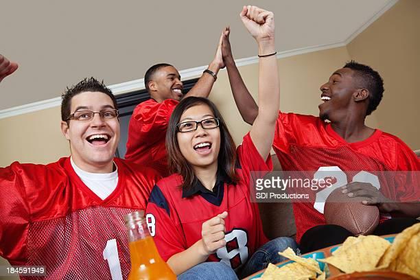Tifosi di calcio in casa guardando la partita in TV