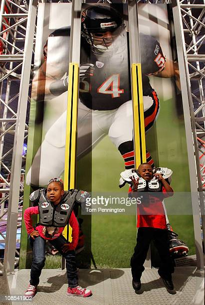 Football fans Azjha Clark and Adarius Clark try on NFL player's shoulder pads at the NFL Experience exhibit at the Dallas Convention Center on...