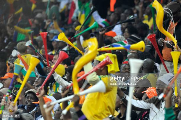Football fans blow vuvuzelas and cheer during the Group G first round 2010 World Cup football match Ivory Coast versus North Korea on June 25 2010 at...