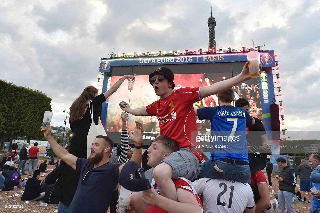 Football fans celebrate as they watch on a giant screen the Euro 2016 round of 16 football match between Hungary and Belgium at the Champs-de-Mars fan zone in Paris on June 26, 2016. / AFP / ALAIN