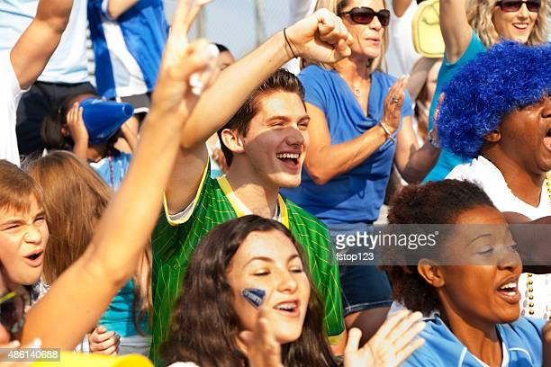 Football fans cheer for their team during sports event. Stadium.