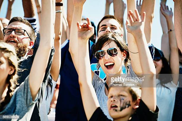 Football fans cheering with arms overhead