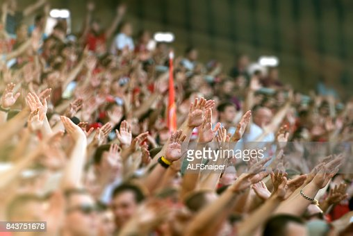 Football fans clapping on the podium of the stadium : Stock Photo