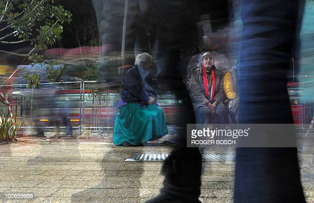 Football fans file past a group of elderly people sitting on a bench as they are on their way into Cape Town Stadium to watch the 2010 Football World...