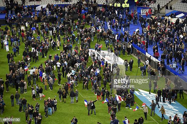Football fans gather in the field as they wait for security clearance to leave the Stade de France in SaintDenis north of Paris after the friendly...