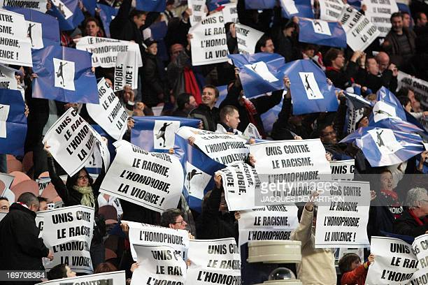 Football fans hold posters reading 'United against racism homophobia and violence' before the French L1 football match Paris SaintGermain vs Lorient...