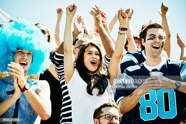 Football fans in stadium celebrating touchdown