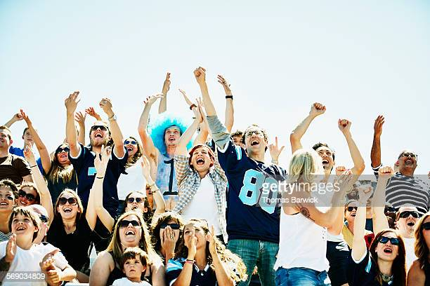 Football fans in stadium cheering during game