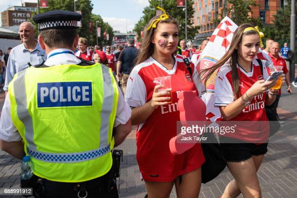 Football fans make their way to Wembley Stadium past a police officer ahead of the FA Cup final on May 27 2017 in London England Football fans will...