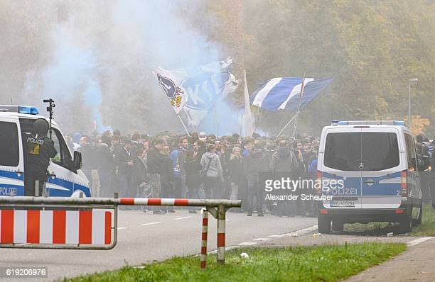 Football fans of Karlsruhe walk to the stadium with police protection and burn flares prior to the Second Bundesliga match between Karlsruher SC and...