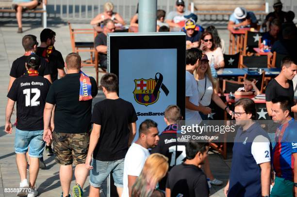 Football fans pass by a Barcelona logo with a black ribbon before the Spanish league footbal match FC Barcelona vs Real Betis at the Camp Nou stadium...