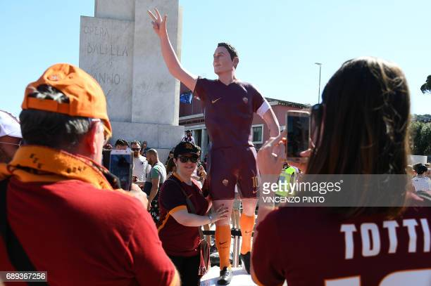Football fans pose with a statue of AS Roma's football star Francesco Totti as they arrive at the Olympic Stadium for the Italian Serie A football...
