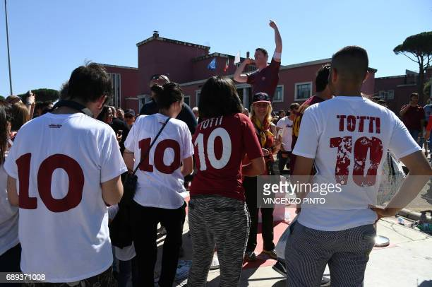 Football fans pose with a statue of AS Roma's number 10 Francesco Totti as they arrive at the Olympic Stadium for the Italian Serie A football match...
