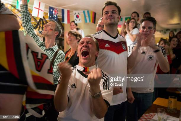 Football fans supporting the German national team celebrate as they watch Germany win the FIFA World Cup on a big screen in the 'Bavarian Beerhouse'...