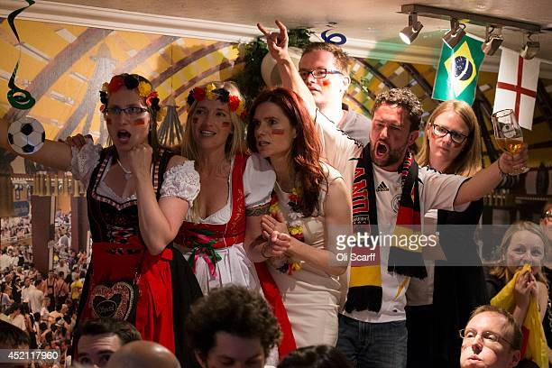 Football fans supporting the German national team celebrate as they watch Germany win the FIFA World Cup on a big screen in the Bavarian Beerhouse...
