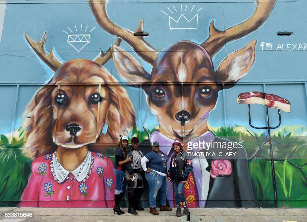TOPSHOT Football fans take photos in front of a graffiticovered building in the Old Chinatown section of downtown near the NFL Experience at the...