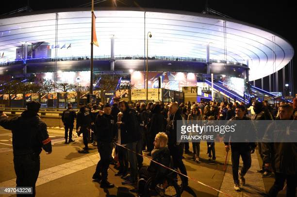Football fans talk to a policeman securing an area outside the Stade de France stadium following the friendly football match between France and...