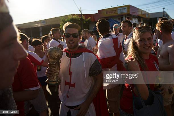 Football fans the majority of whom support England dance and cheer with a replica World Cup before England's opening game in the FIFA World Cup on...