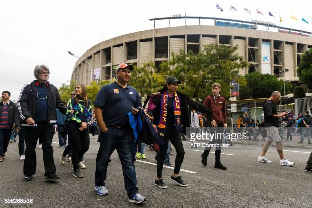 Football fans walk outside the Camp Nou after the decission of playing behind closed doors the Spanish league football match FC Barcelona vs UD Las...