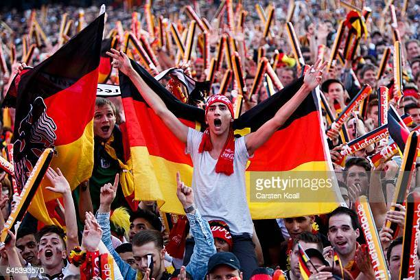 Football fans watch the 2016 UEFA European Championship match between Germany and France at a public viewing area on a large outdoor screen at...