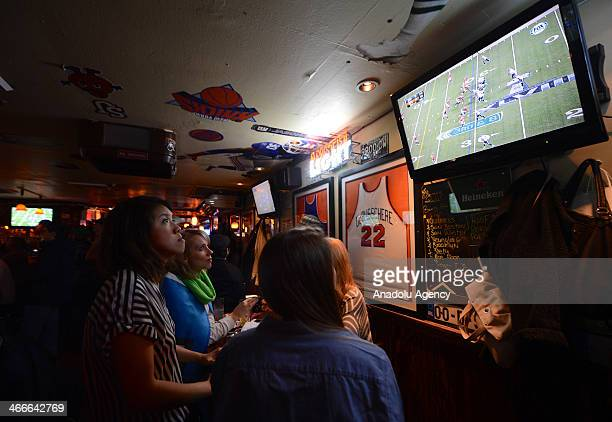 Football fans watch the NFL Super Bowl XLVIII game between the Denver Broncos and the Seattle Seahawks on television at a sports bar in New Jersey...