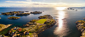 Aerial view of Henningsvaer, its scenic football field and many fish racks at sunset. Henningsvaer is a fishing village located on several small islands in the Lofoten archipelago in Norway