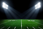 Football field at night with stadium lights.