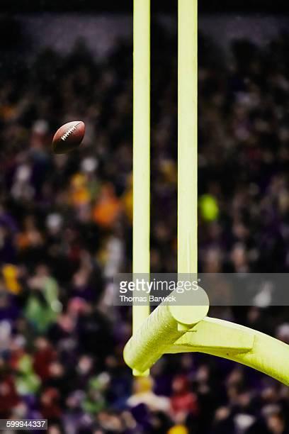 Football flying through goal posts in stadium