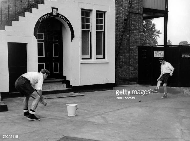 Jimmy Hill and Johnny Haynes enjoy a friendly kick around with a ball and a bucket in the back yard of Craven Cottage