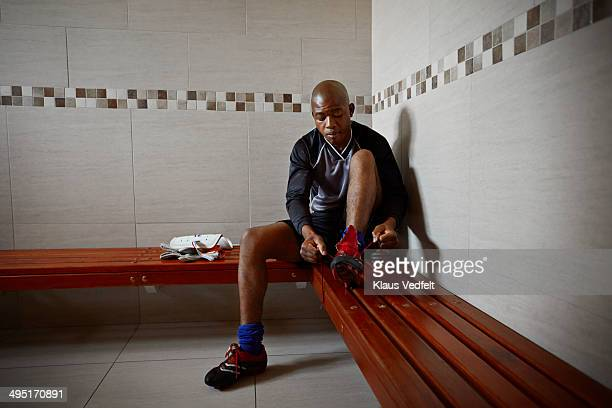Football goal keeper tying shoes in changing room