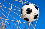 Football or soccer goal, with a neutral design ball flying into the net and blue sky in the background