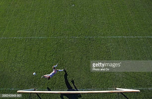 Football goalie blocking goal, overhead view