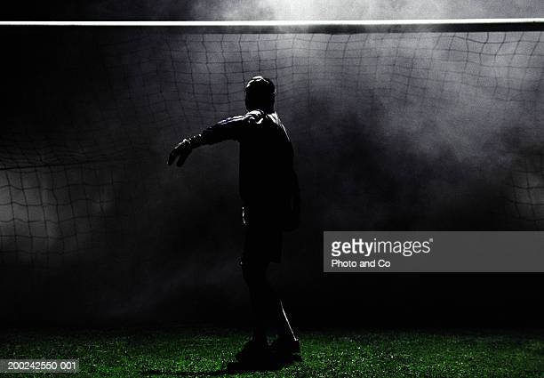 Football goalie preparing to throw ball, night