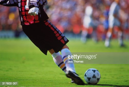 Football goalkeeper about to kick ball, low section, close-up
