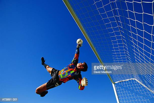 Football goalkeeper diving for ball, low angle view (Enhancement)