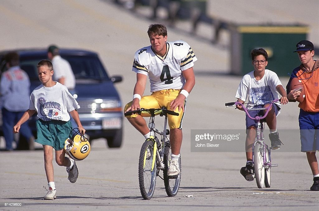 Green Bay Packers QB Brett Favre (4) with fans riding bicycle to training camp at St, Norbert College, De Pere, WI 7/21/1993
